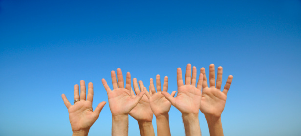 People's hands in air, palms outstretched,